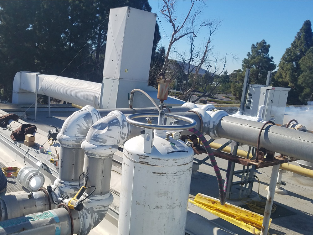 "Roof top cooling system with 6"" pipe freeze plug in background"