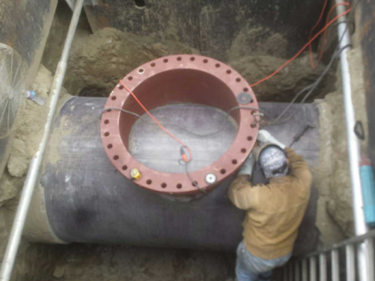 Another view welding the 54 inch fitting onto the steel in the concrete pipeline